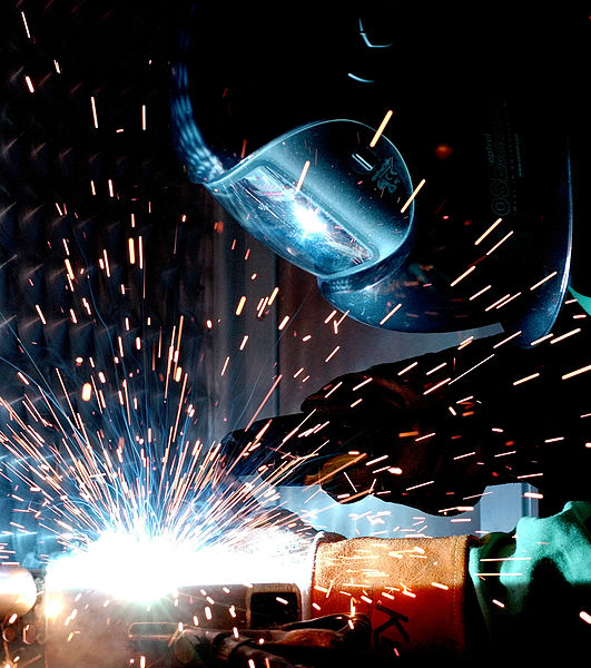 A man gas metal arc welding (MIG)-credit-by William M. Plate Jr. [Public domain], via Wikimedia Commons