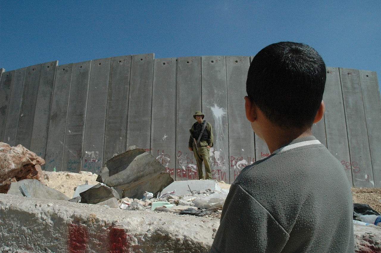 Boy_and_soldier_in_front_of_Israeli_wall_Credit_Justin_McIntosh