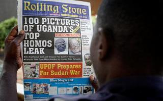 A Ugandan man reads the headline of the Rolling Stone newspaper which calls for gay people to be hanged. Photograph: AP